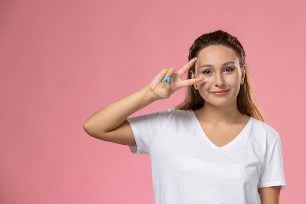 ピンクの背景にポーズをとって白いtシャツsmiで正面の若い魅力的な女性