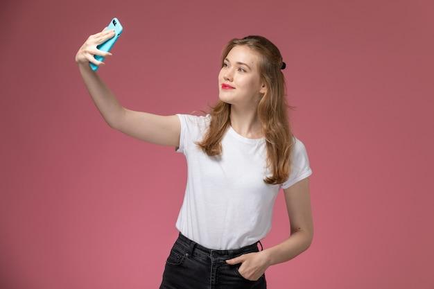 ピンクの壁のモデル色の女性の女の子に自分撮りを取っている白いtシャツの正面図若い魅力的な女性