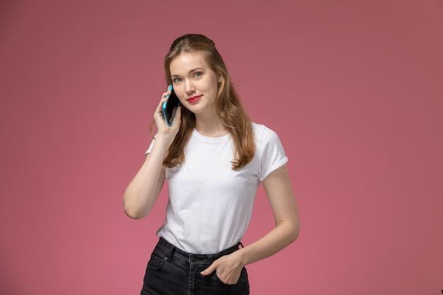 ピンクの壁のモデルの女性のポーズのカラー写真の女性の若いで電話で話している白いtシャツの正面図若い魅力的な女性