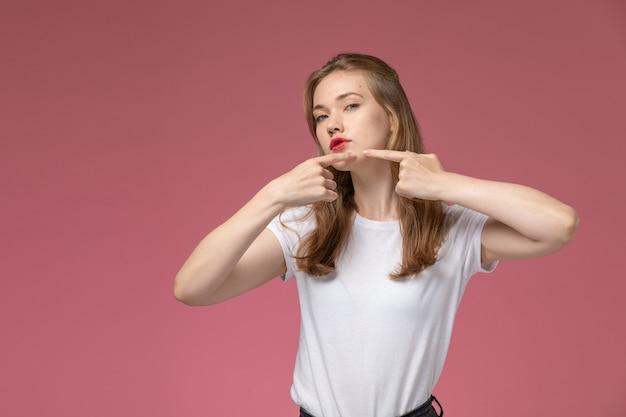 Вид спереди молодая привлекательная женщина в белой футболке, касаясь ее прыщей на темно-розовой стене, цвет модели женщина молодая девушка