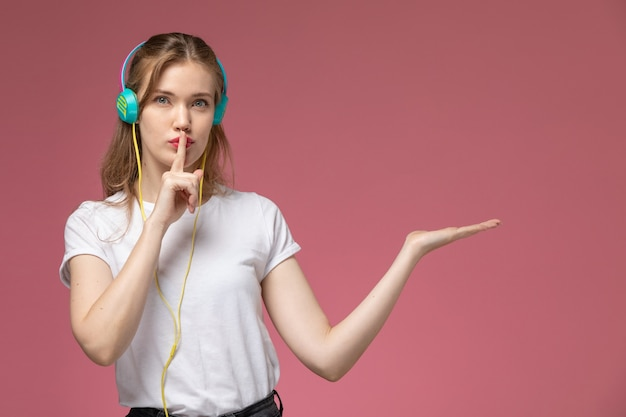 Front view young attractive female listening to music and showing silence sign on the pink wall model color female young girl