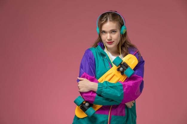 Вид спереди молодая привлекательная женщина, слушающая музыку в цветном пальто, держащая скейтборд на розовой стене, модель цвета девушки, молодая девушка