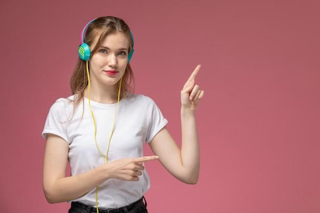Вид спереди молодая привлекательная женщина, слушающая музыку через наушники с легкой улыбкой на темно-розовой стене, цвет модели женщина молодая девушка