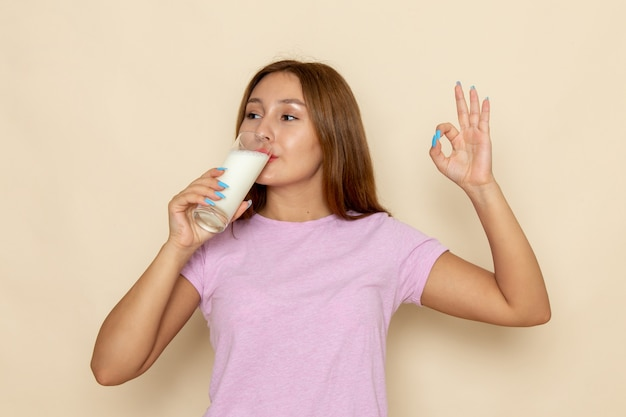 Front view young attractive female in pink t-shirt and blue jeans drinking milk