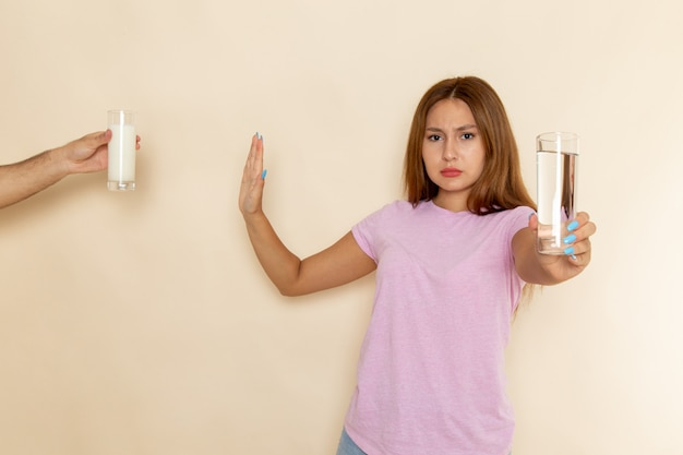 Front view young attractive female in pink t-shirt and blue jeans holding glass of water and denying milk