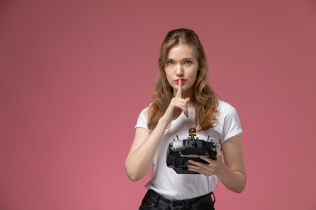 Front view young attractive female showing silence sign holding remote controller on pink wall model color female young girl