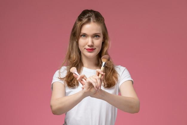 ピンクの壁のモデルの色の女性の若い女の子に化粧ブラシを保持している笑顔の若い魅力的な女性の正面図