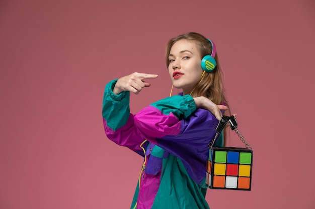 Vista frontale giovane femmina attraente che indossa cappotto colorato ascoltando musica sulla parete rosa scuro modello colore femmina giovane ragazza