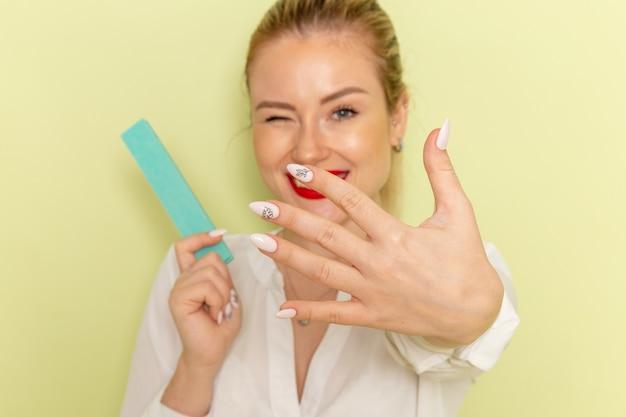 Giovane femmina attraente di vista frontale in camicia bianca che ripara le sue unghie sulla superficie verde