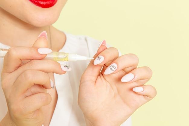 Giovane femmina attraente di vista frontale in camicia bianca che lavora con le sue unghie sulla superficie verde