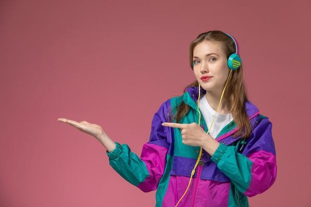 Vista frontale giovane femmina attraente in t-shirt bianca cappotto colorato ascoltando musica su scrivania rosa modello femmina colore femmina giovane