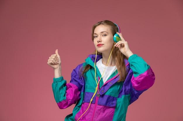 Vista frontale giovane femmina attraente in t-shirt bianca cappotto colorato ascoltando musica sul muro rosa modello colore femmina giovane