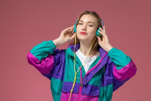Vista frontale giovane femmina attraente in t-shirt bianca cappotto colorato ascoltando musica sul muro rosa modello femmina posa colore femmina giovane