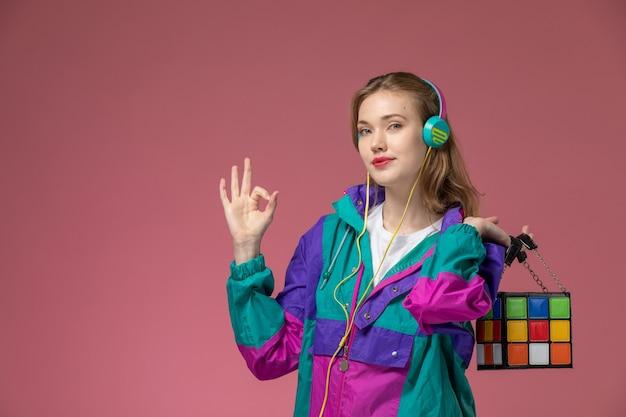 Vista frontale giovane donna attraente in t-shirt bianca cappotto colorato ascoltando musica tramite auricolari con sorriso sulla parete rosa modello femmina posa foto a colori