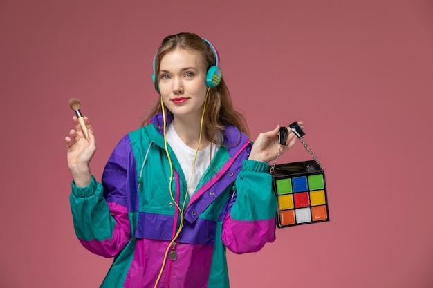 Vista frontale giovane femmina attraente in t-shirt bianca cappotto colorato ascoltando musica con gli auricolari sul muro rosa modello femmina posa foto a colori