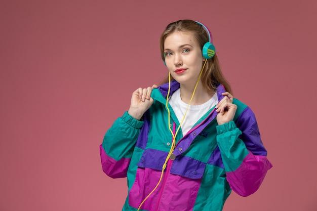 Giovane femmina attraente di vista frontale in cappotto colorato della maglietta bianca che ascolta la musica con il sorriso sulla foto a colori di posa femminile del modello della scrivania rosa