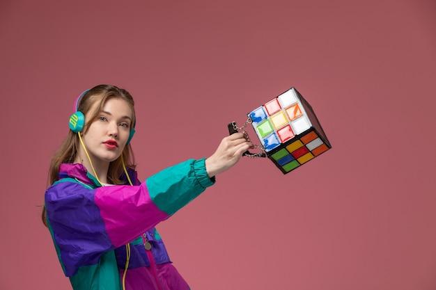 Giovane femmina attraente di vista frontale in cappotto colorato della maglietta bianca che posa ascoltando la borsa della tenuta di musica sul colore di posa femminile del modello della parete rosa