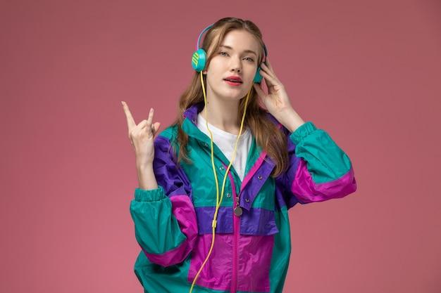 Vista frontale giovane femmina attraente in t-shirt bianca cappotto colorato in posa ascoltando musica sulla scrivania rosa modello femmina posa foto a colori