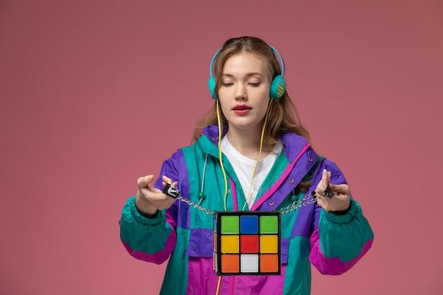 Vista frontale giovane femmina attraente in t-shirt bianca cappotto colorato in posa ascoltando musica sulla parete rosa modello femmina posa foto a colori