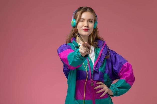 Vista frontale giovane femmina attraente in t-shirt bianca cappotto colorato in posa ascoltando musica con il sorriso sulla parete rosa modello femmina posa foto a colori