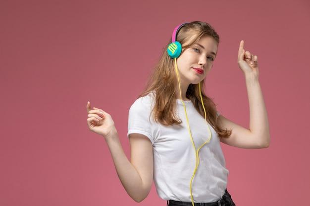 Giovane femmina attraente di vista frontale in maglietta bianca ballando e ascoltando musica sulla ragazza femminile di colore rosa scuro del modello della parete