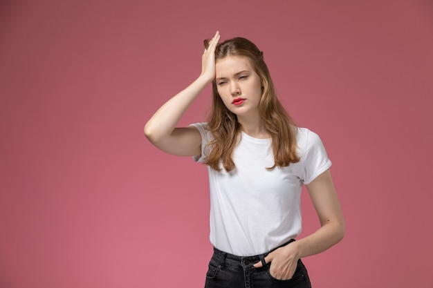 Front view young attractive female in white t-shirt having a severe headache on the pink wall model female pose color photo