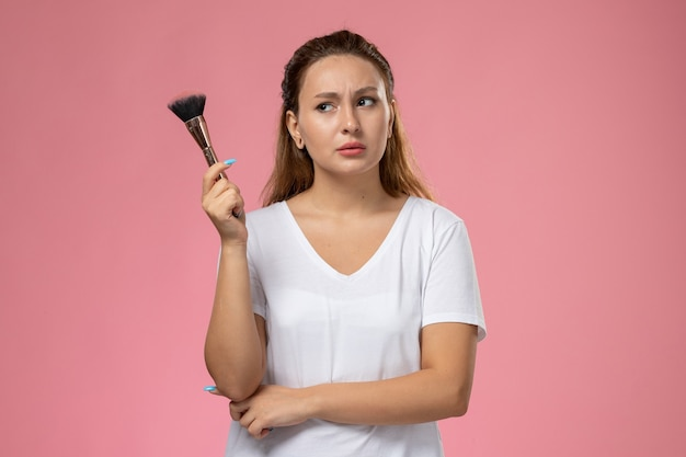 Front view young attractive female in white t-shirt holding make-up brush on the pink background