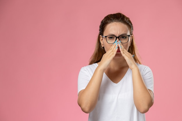 Front view young attractive female in white t-shirt just posing and covering her nose on the pink background