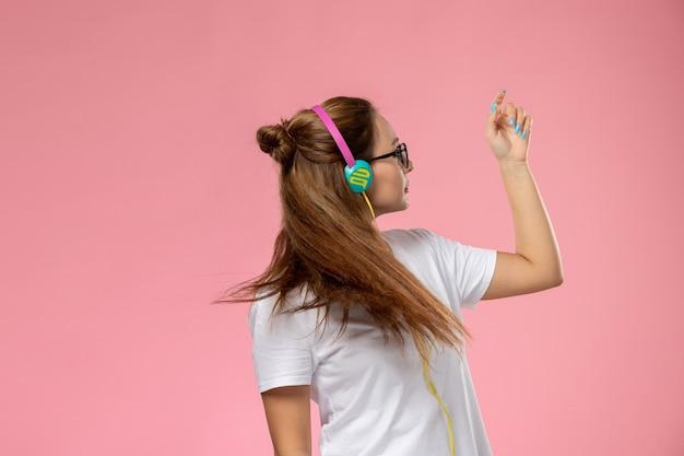 Giovane donna attraente di vista frontale in maglietta bianca che posa e ascolta la musica tramite auricolari e balla sullo sfondo rosa
