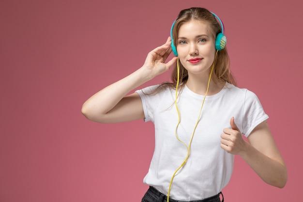 Giovane femmina attraente di vista frontale in maglietta bianca che ascolta la musica sulla ragazza femmina di colore rosa scuro del modello della scrivania