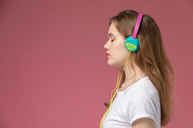 Giovane femmina attraente di vista frontale in maglietta bianca che ascolta la musica sulla ragazza della femmina di colore del modello della parete rosa scuro