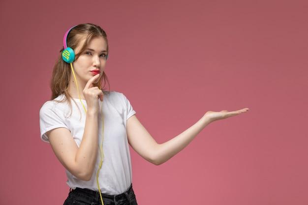 Giovane femmina attraente di vista frontale in maglietta bianca che ascolta la musica sui giovani della femmina di colore del modello della parete rosa