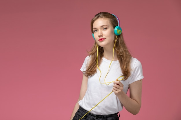 Front view young attractive female in white t-shirt listening to music with slight smile on the dark-pink wall model color female young girl