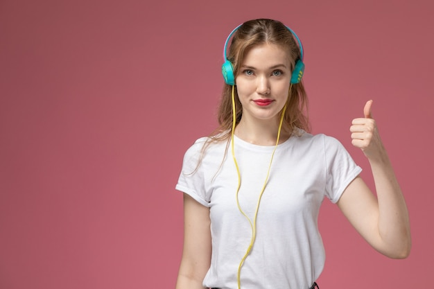 Front view young attractive female in white t-shirt listening to music with slight smile on pink desk model color female young girl
