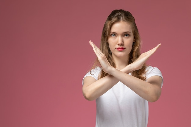 Front view young attractive female in white t-shirt posing showing ban sign on pink wall model female pose color photo