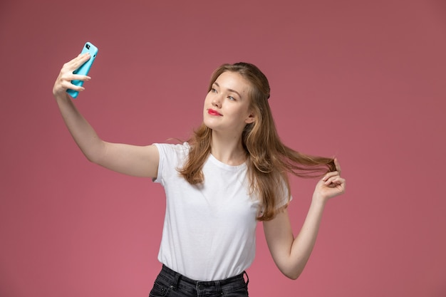 Front view young attractive female in white t-shirt posing and taking a selfie on the pink wall model color female young girl