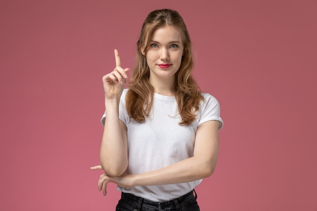 Front view young attractive female in white t-shirt posing with delighted expression on pink wall model female pose color female young