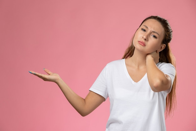 Front view young attractive female in white t-shirt suffering from neck ache on pink background