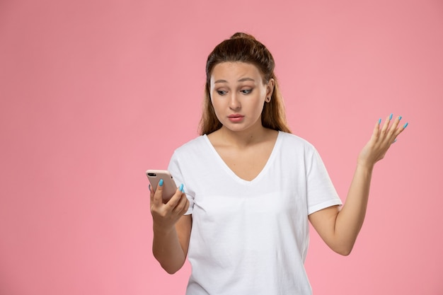 Front view young attractive female in white t-shirt using her phone on pink background