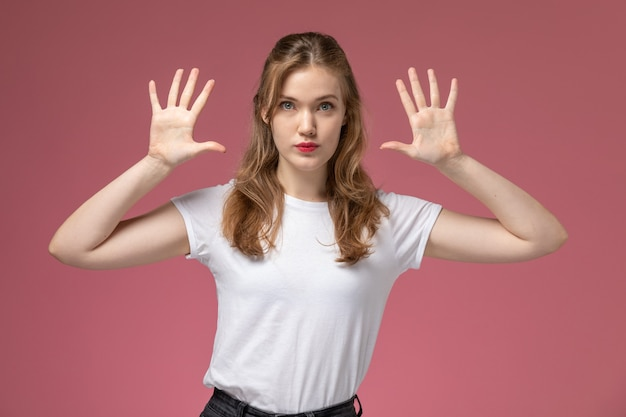 Front view young attractive female in white t-shirt with raised hands posing on the pink wall model color female young
