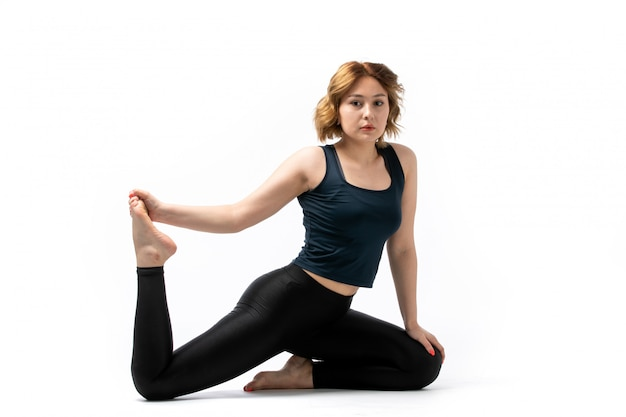 A front view young attractive girl in blue shirt and black trousers sport outfit doing workouts on the white