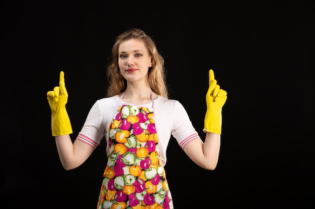 Una giovane ragazza attraente di vista frontale in capo variopinto che sorride indossando i guanti gialli sui precedenti neri ama la positività di sorriso