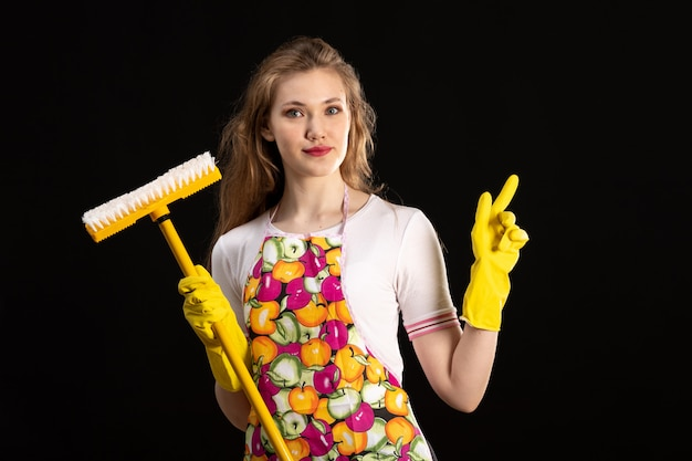 A front view young attractive girl in colorful cape smiling wearing yellow gloves holding yellow mop on the black background love smile positivity