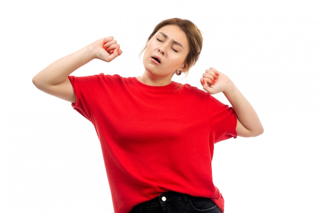 A front view young attractive girl in red t-shirt wearing black jeans wanting to sleep sneezing on the white