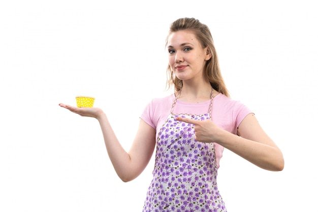 A front view young attractive housewife in pink shirt colorful cape holding yellow thing smiling on the white background cuisine kitchen female