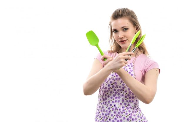 Una giovane casalinga attraente di vista frontale in capo variopinto della camicia rosa che posa tenendo gli elettrodomestici da cucina di plastica sulla femmina bianca della cucina di cucina del fondo