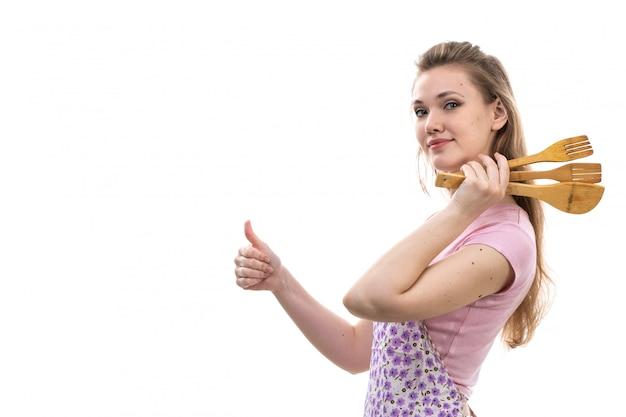 Una giovane casalinga attraente di vista frontale nella posa sorridente del capo variopinto della camicia rosa che tiene gli apparecchi di legno sulla femmina bianca della cucina di cucina del fondo
