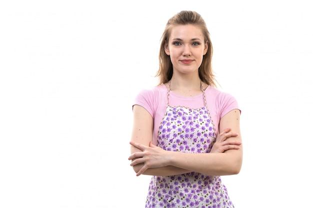 Una giovane casalinga attraente di vista frontale nella posa sorridente del capo variopinto della camicia rosa sulla femmina bianca della cucina di cucina del fondo