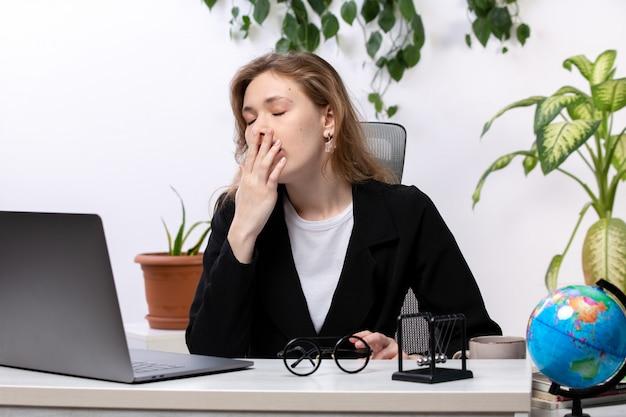 Una giovane donna attraente di vista frontale in giacca nera e camicia bianca davanti al tavolo di lavoro con laptop starnuti tecnologie di lavoro aziendale