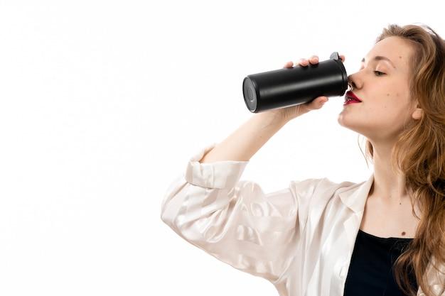 Una giovane signora attraente di vista frontale in camicia nera e pantaloni neri che tengono termos nero che beve sul bianco